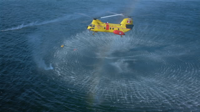 Aerial CH-113 Labrador Canadian SAR helicopter hovering over raft in water / British Columbia