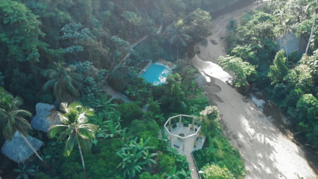 aerial: charming tree houses and bright blue swimming pool in exotic jungle - hispaniola stock videos & royalty-free footage