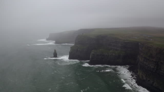 aerial: chilly waves crashing on rough cliff wall in misty winter in kerry, ireland - fog stock videos & royalty-free footage