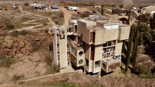 vidéos et rushes de ws aerial circle around visitor center building at arcosanti futuristic town by architect paolo soleri in arizona desert - centre culturel