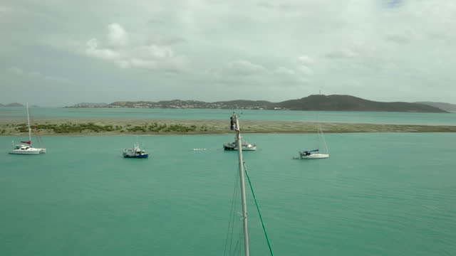 aerial circling a man clinging to the top of a ship's mast moored in a harbor and surrounded by blue-green seas, shoreline, and other boats nearby - cape york, australia - other点の映像素材/bロール