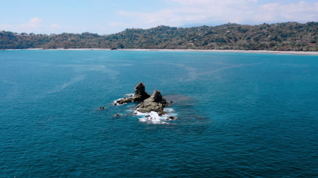 aerial: circling around jagged rocks sticking out of ocean near beach and lush hills - playa espadilla, costa rica - costa rica stock videos & royalty-free footage