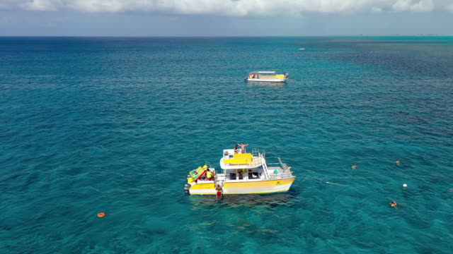 aerial: circling around yellow pontoon boat and tourists swimming near boat in tropical water - providenciales, turks and caicos - turks and caicos islands stock videos & royalty-free footage