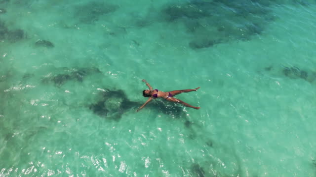 aerial circling: beautiful young woman in bikini floating in crystal clear ocean - 水平アングル点の映像素材/bロール