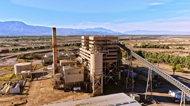 ws aerial circling biomass power plant generating electricity from biological urban wood waste near railroad track with freight train passing by - fuel and power generation stock-videos und b-roll-filmmaterial