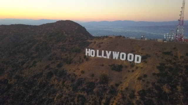 aerial circling: iconic hollywood sign at dusk in los angeles, california - berühmte persönlichkeit stock-videos und b-roll-filmmaterial