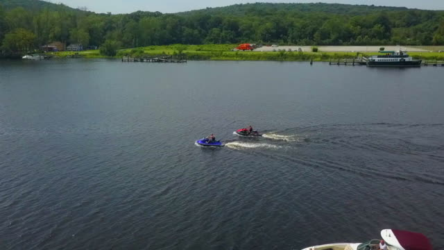 aerial: circling jet skis in front of swing bridge and goodspeed opera house - swing bridge stock videos & royalty-free footage