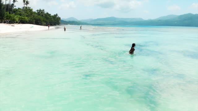 vídeos y material grabado en eventos de stock de aerial circling: people on stunning tropical beach with crystal clear water - tumbona