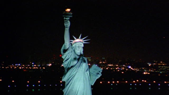 Aerial circling Statue of Liberty at night