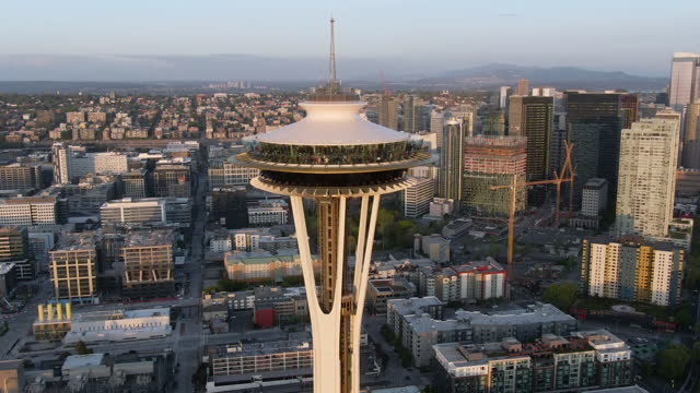 aerial circling the space needle observation deck with the entire city in the background including downtown skyline, elliott bay, and the sprawling city suburbs stretching to the horizon in the light of a setting sun - seattle, washington - スペースニードル点の映像素材/bロール