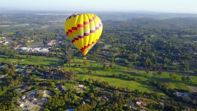 vídeos de stock, filmes e b-roll de aerial circling yellow hot air balloon - plano geral ponto de vista