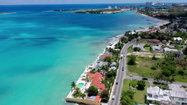 aerial: city of nassau and waterfront homes looking over gorgeous blue tropical water - nassau stock videos & royalty-free footage