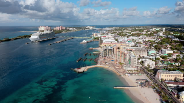 aerial: cityscape of nassau, beach, hotels, and huge cruise ship docked near shore - bahamas stock videos & royalty-free footage