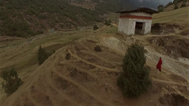 aerial clip of monk walking on mountain in bhutan - bhutan stock videos & royalty-free footage
