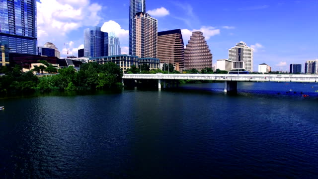 vídeos de stock e filmes b-roll de aerial: close to water over town lake austin texas flying towards downtown skyline cityscape with deep blue water and sky - town
