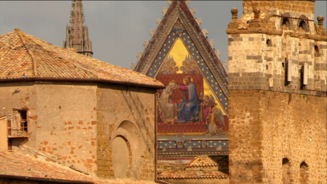 aerial close up mosaic and bas-reliefs on facade of gothic cathedral / orvieto, italy - ウンブリア州点の映像素材/bロール