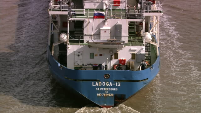 vidéos et rushes de aerial close up name of russian dry freighter on stern / zoom out over ship approaching swing bridge on nene - équipage de bateau