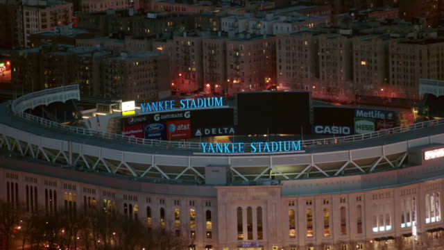 aerial close up of yankee stadium with zoom out to reveal the bronx at night, nyc - 北アメリカ点の映像素材/bロール