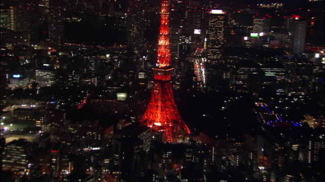 Aerial close up Tokyo Tower lights at night/ zoom out tower and cityscape/ over Mori Tower/ Tokyo / November 16, 2005