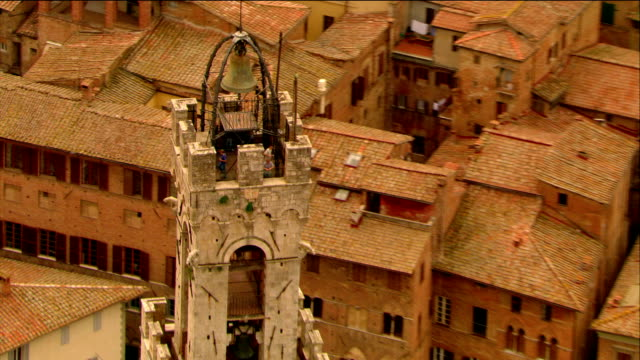aerial close up tourists looking out from torre del mangia / pull out to palazzo pubblico / siena, italy - palazzo pubblico stock videos and b-roll footage