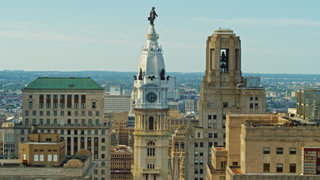 aerial close view on city hall with the william penn statue atop of the tower in front of cityscape of philadelphia, pennsylvania. drone video with the forward and ascending camera motion. - william penn stock videos & royalty-free footage