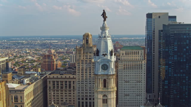 aerial close view on philadelphia city hall with the william penn statue atop of the tower in front of the residential districts of philadelphia, pennsylvania. drone video with the descending camera motion. - philadelphia pennsylvania stock videos & royalty-free footage