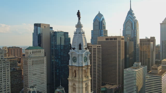 aerial close view on philadelphia city hall with the william penn statue atop of the tower in front of downtown district, philadelphia, pennsylvania. drone video with the panning camera motion. - william penn stock videos & royalty-free footage