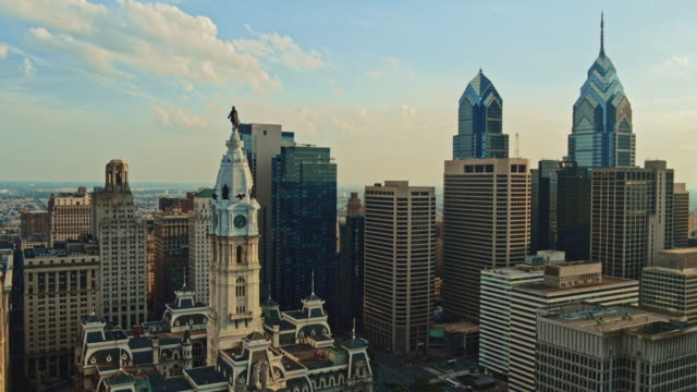 aerial close view on philadelphia city hall with the william penn statue atop of the tower in front of downtown district, philadelphia, pennsylvania. drone video with the backward camera motion. - william penn stock videos & royalty-free footage