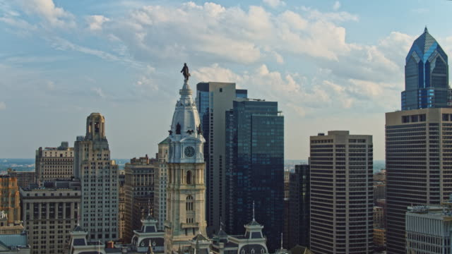 aerial close view on philadelphia city hall with the william penn statue atop of the tower in front of downtown district, philadelphia, pennsylvania. drone video with the complex backward and panning camera motion. - william penn stock videos & royalty-free footage