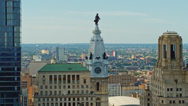 aerial close view on philadelphia city hall with the william penn statue atop of the tower in front of the cityscape of philadelphia, pennsylvania. drone video with the panning camera motion. - william penn stock videos & royalty-free footage
