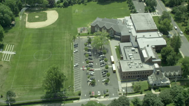 vidéos et rushes de aerial close-up orbit of school and soccer field to pan out - school building
