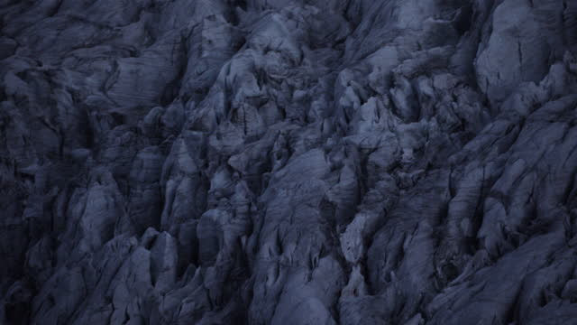 aerial, close-up view of the jagged side of a glacier in the swiss alps at sunrise. - helicopter point of view stock videos & royalty-free footage