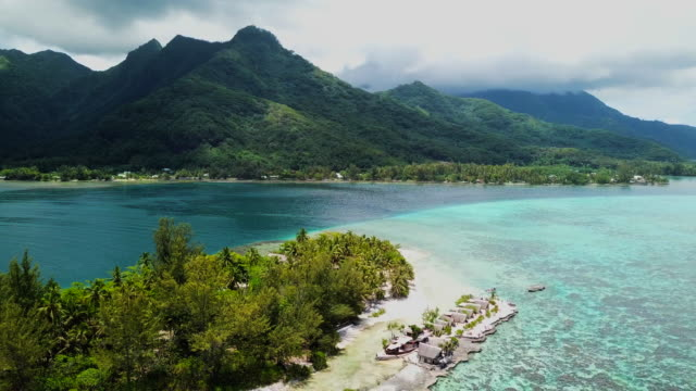 aerial: clouds hover over the top of the lush mountain on moorea island - moorea stock videos & royalty-free footage