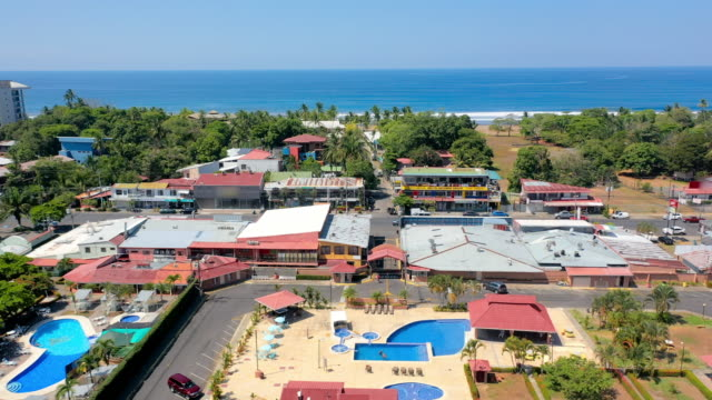 aerial: coastal town of jaco, hotels with swimming pools situated near the beach - 南アメリカ点の映像素材/bロール