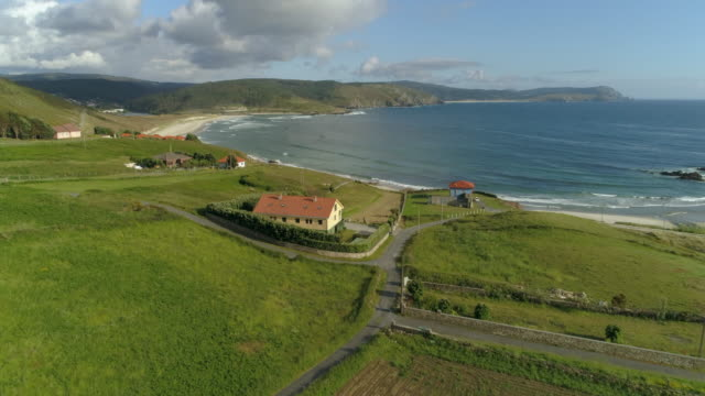 aerial: coastal village with houses and sea against sky on sunny day - galicia, spain - galicia stock videos & royalty-free footage