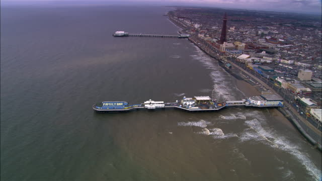 stockvideo's en b-roll-footage met aerial coastline and piers/ overhead pier/ blackpool, england - blackpool lancashire