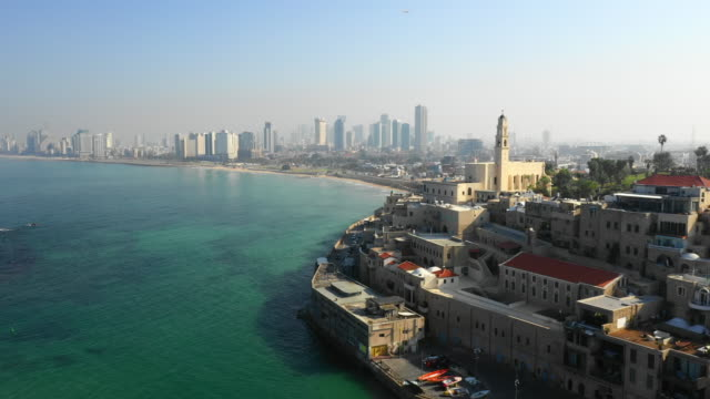 aerial: coastline by tel aviv and jaffa with view of old architecture and city skyline - テルアビブ点の映像素材/bロール