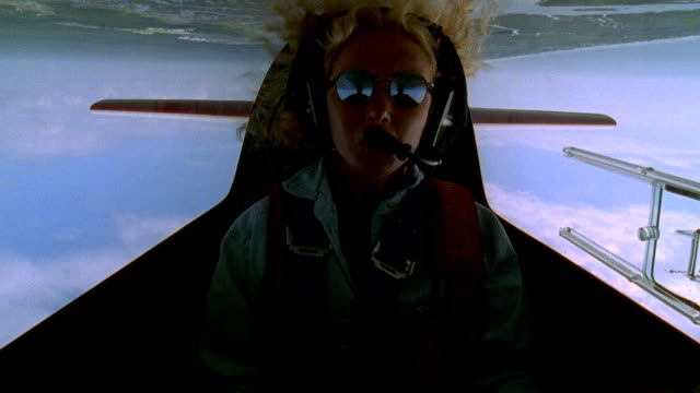 aerial cockpit point of view medium shot female pilot in cockpit of small airplane performing stunts during flight - captain stock videos & royalty-free footage