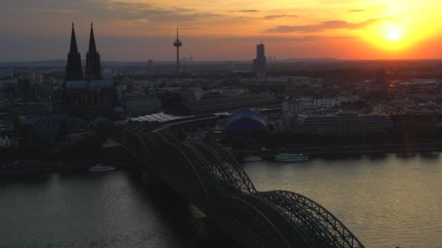 aerial köln dom hohenzollernbrücke bei sonnenuntergang deutschland - kathedrale stock-videos und b-roll-filmmaterial