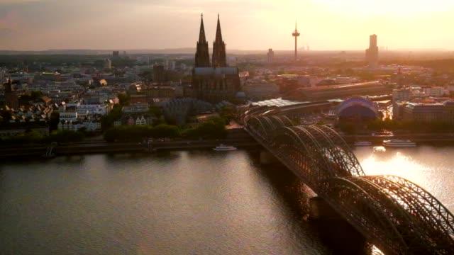 vídeos de stock e filmes b-roll de aerial cologne cathedral hohenzollern bridge at sunset germany - rio reno