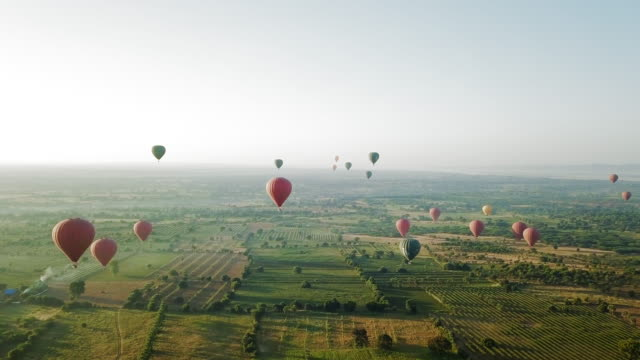 vídeos de stock e filmes b-roll de aerial: colorful hot air balloons soaring over old bagan - morno