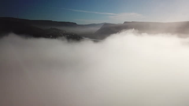 aerial: coming out of a thick cloud revealing mountain - thick stock videos & royalty-free footage