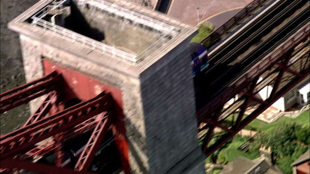 vidéos et rushes de aerial commuter train crossing forth bridge / pull out to view of bridge over river / edinburgh - train de banlieue