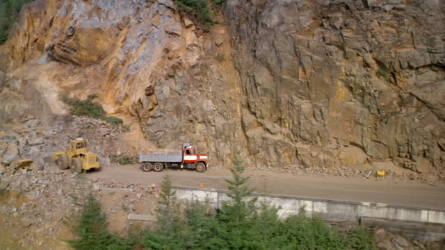Aerial construction crew cleaning up rockslide on highway / British Columbia, Canada
