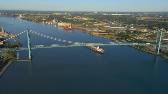 Aerial WS Container ship transporting ore across Detroit River near Ambassador Bridge / Detroit, Michigan, USA