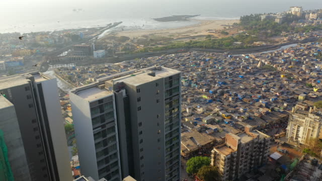 aerial: contrasts neighborhoods by sea in city - mumbai, india - slum stock videos & royalty-free footage