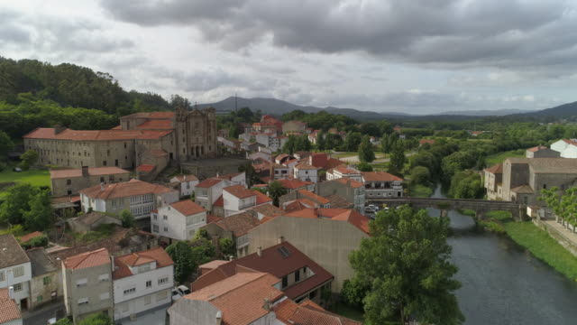 aerial: convento del carmen amidst buildings by sar river in town against cloudy sky - padron, spain - 女子修道院点の映像素材/bロール