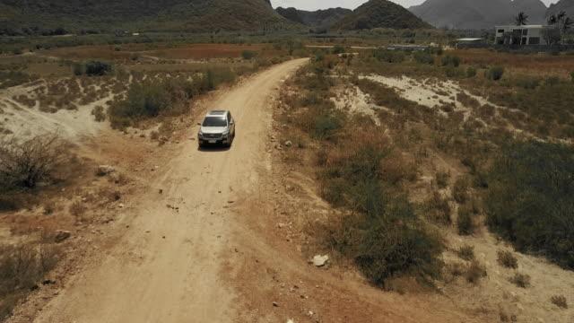 vídeos de stock e filmes b-roll de aerial country road driving - carro 4x4