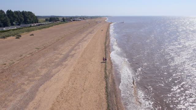 aerial couple walking along heacham beach - norfolk england stock videos & royalty-free footage