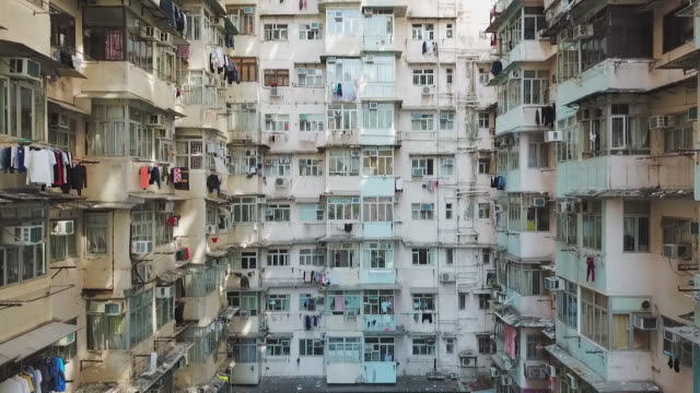 aerial: courtyard of multiple story high-rise apartment building in hong kong - hanging stock videos & royalty-free footage